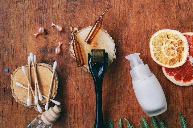 Dermaroller e siero accanto a una crema per il viso antietà per l'industria della bellezza