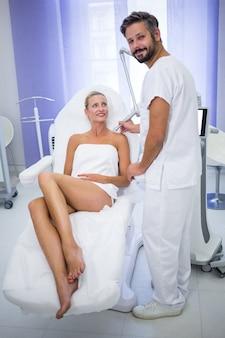 Dermatologo che rimuove talpa dalla spalla della donna