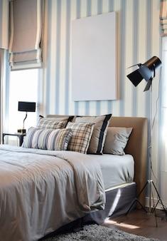 Design elegante camera da letto con cuscini a righe sul letto e lampada da tavolo decorativa.