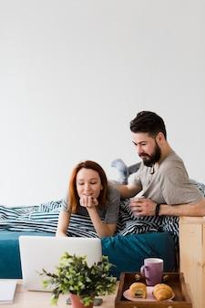 Design minimalista camera da letto e coppia con computer portatile