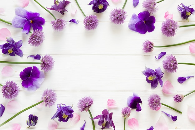 Design piatto di fiori, fiori viola e rosa su tavola di legno bianca, cornice floreale in stile piatto con posto per il testo