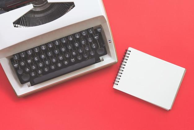 Design piatto di macchina da scrivere e taccuino in bianco su sfondo rosso. stile retrò.