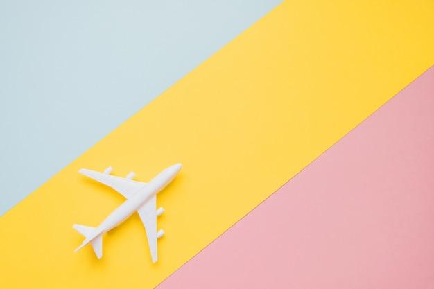 Design piatto laici del concetto di viaggio con aereo e nuvola su blu, giallo e rosa