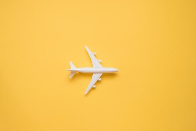 Design piatto laici del concetto di viaggio con aereo su giallo