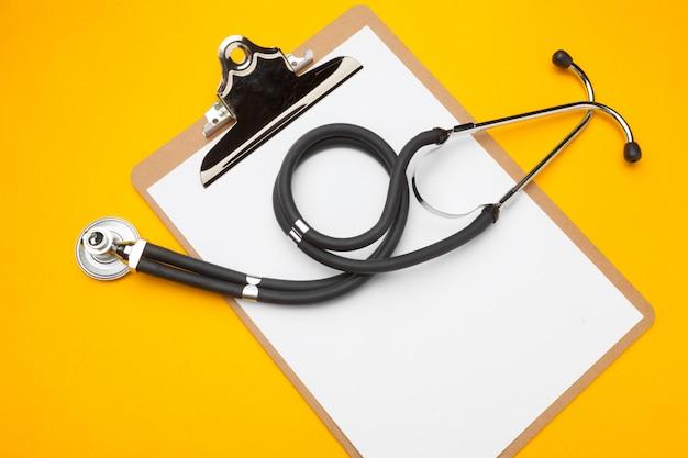 Design piatto laico di stetoscopio e blocco appunti vuoto