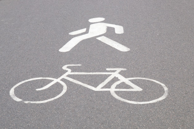 Designazione di una pista ciclabile e di un passaggio pedonale dipinto di vernice bianca sull'asfalto