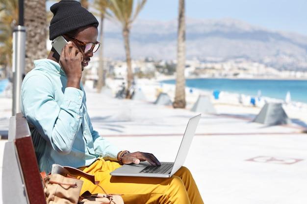 Designer afroamericano dall'aspetto alla moda, seduto su una panchina all'aperto in riva al mare, lavorando da remoto sul computer portatile e avendo una conversazione telefonica in una giornata di sole mentre trascorre le vacanze in località turistica