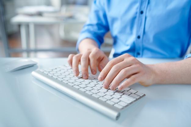 Designer creativo in camicia blu, toccando i pulsanti della tastiera del computer mentre si lavora al progetto creativo