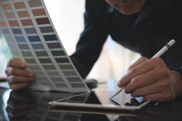 Designer d'interni di casa utilizzando la tavoletta digitale che lavora in ufficio