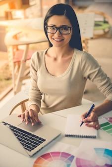 Designer di abbigliamento casual e occhiali da vista utilizza laptop