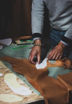 Designer di scarpe che lavora con la pelle.