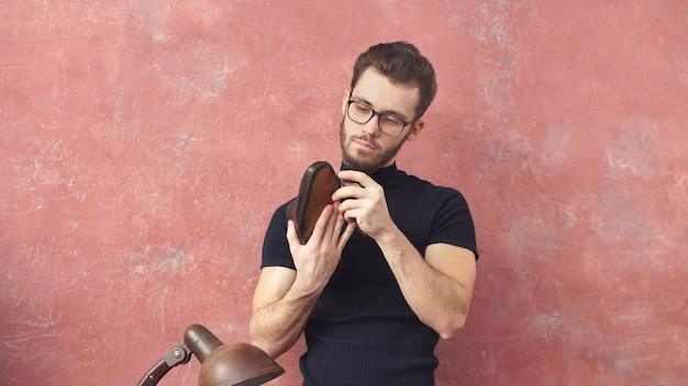 Designer di talento detiene stivali e controlla il suo lavoro, lavoro, professione
