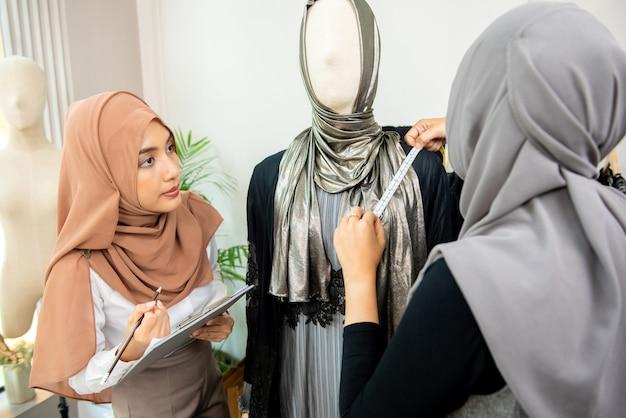 Designer donna musulmana che lavora con il collega che misura la taglia del vestito