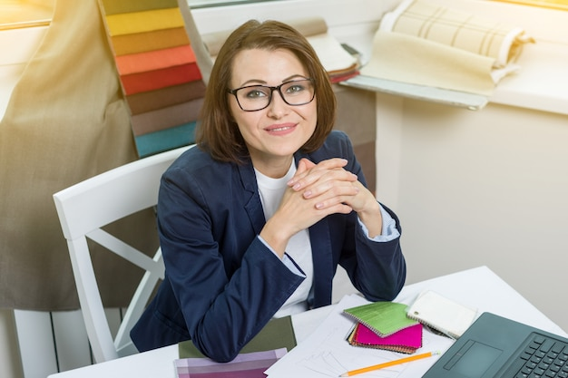 Designer o architetto in posa e ti guardano seduto in ufficio
