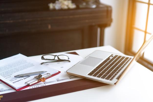 Desktop aziendale con laptop, occhiali, business plan