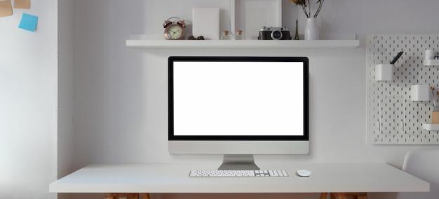 Desktop computer dello schermo in bianco nella stanza dell'ufficio moderna con articoli per ufficio