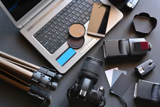Desktop con attrezzatura fotografica, fotocamera, treppiede, flash e computer