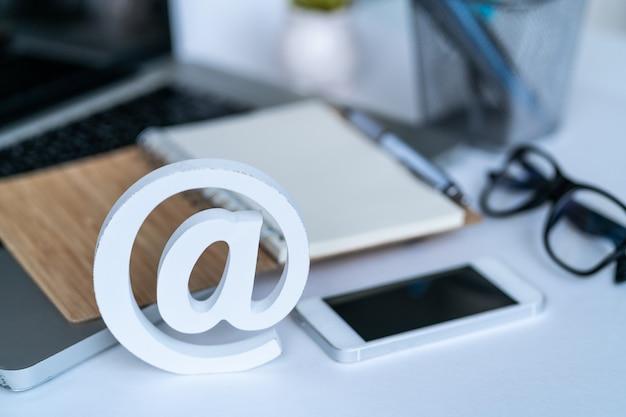 Desktop con blocco note, smartphone, occhiali e simbolo e-mail.