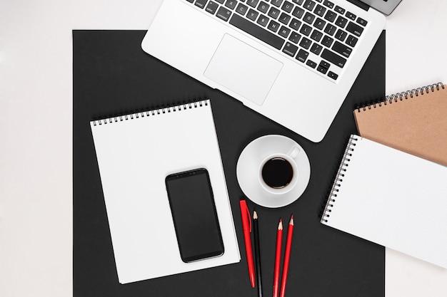 Desktop con laptop, auricolari, calcolatrice, penne, matite, carta, telefono isolato su bianco e nero