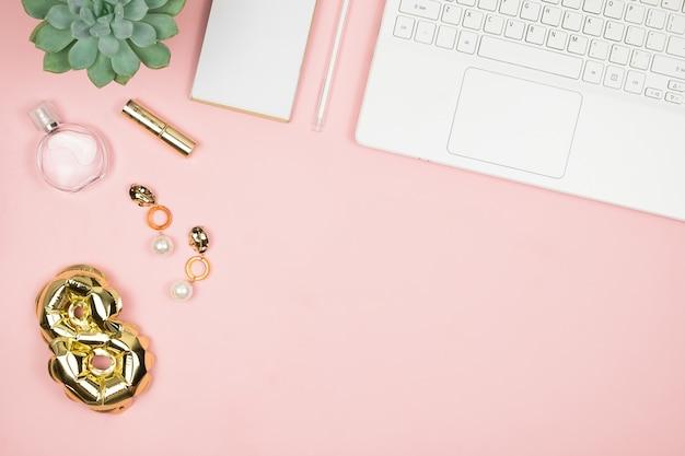 Desktop da donna con laptop, profumo, lamina d'oro ballon 8 e copyspace. vista dall'alto. felice giorno delle donne. complimenti 8 marzo.