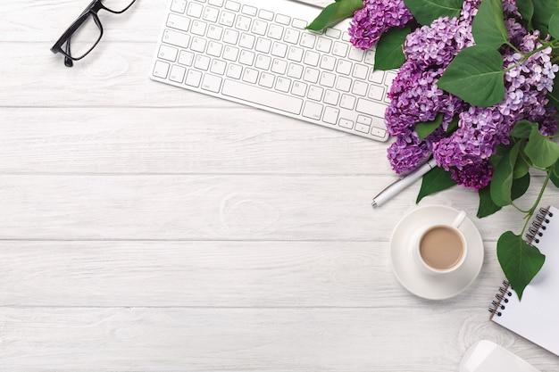 Desktop dell'ufficio con un mazzo di lillà, tazza di caffè, tastiera, taccuino e penna su lavagne bianche