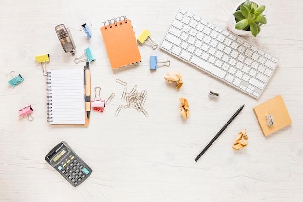 Desktop disordinato con stazionario e tastiera