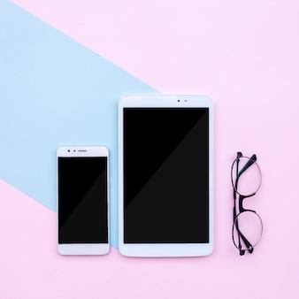 Desktop moderno con telefono e tablet e occhiali su sfondo blu chiaro e rosa