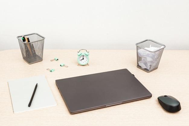 Desktop per studente o libero professionista. spazio di lavoro. posto di lavoro con il computer portatile, il quaderno e l'orologio moderni grigi per controllo di tempo sul tavolo luminoso. messa a fuoco selettiva.
