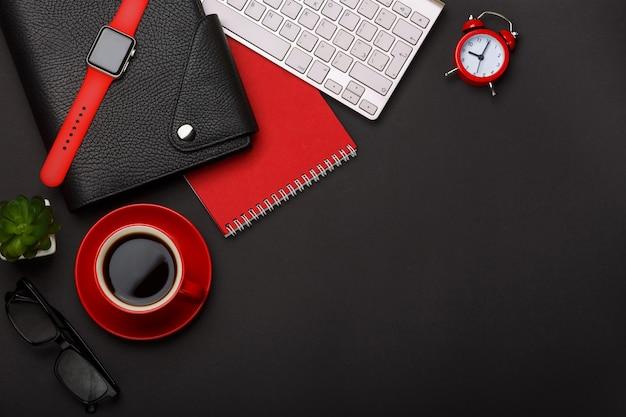 Desktop rosso dello spazio in bianco dell'angolo della tastiera delle cicatrici del diario del fiore della sveglia del blocco note della tazza di caffè del fondo nero