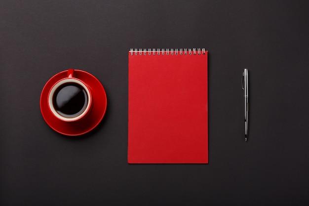 Desktop rosso dello spazio in bianco della maniglia del taccuino della tazza di caffè del fondo nero