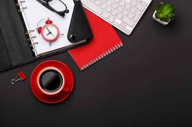 Desktop rosso dello spazio vuoto della tastiera dei punteggi del diario del fiore della sveglia del blocco note della tazza di caffè del fondo nero