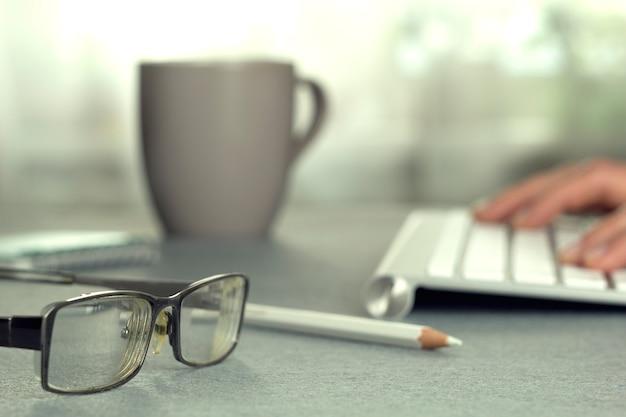 Desktop. tastiera, occhiali e una tazza.
