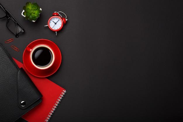 Desktop vuoto del posto del vetro rosso del diario del fiore della sveglia del blocco note della tazza di caffè del fondo nero