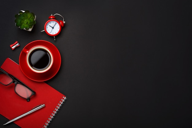 Desktop vuoto dello spazio del fiore rosso della sveglia del blocco note della tazza di caffè del fondo nero