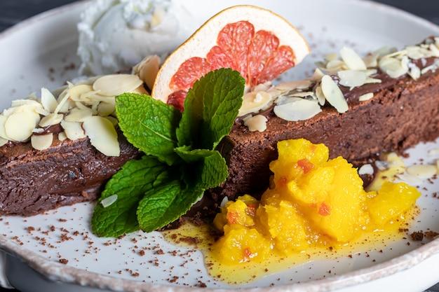 Dessert al cioccolato brownie con una pallina di gelato bianco, fette di mango e una fetta di pompelmo. sullo sfondo c'è un cappuccino. su uno sfondo scuro