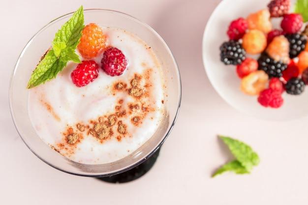 Dessert al latte con frutti di bosco in bicchieri alti