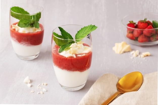 Dessert allo yogurt con purea di fragole e merengue in due bicchieri