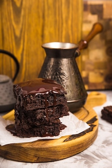 Dessert con cacao brownies in cioccolato vicino a teiera e caffè turk
