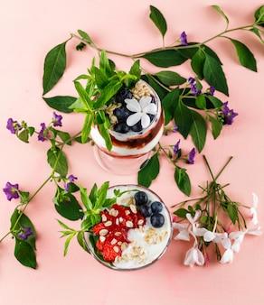 Dessert con fragole, mirtilli, noci, menta, rami di fiori in calice e vaso su superficie rosa, piatto disteso.