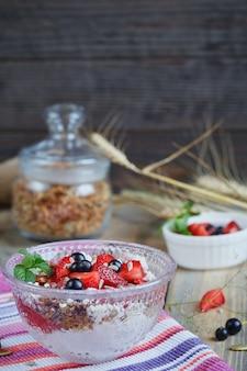 Dessert con frutti di bosco freschi, ricotta, muesli e marmellata di frutti di bosco.