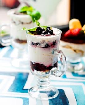 Dessert con panna e frutti di bosco in vetro