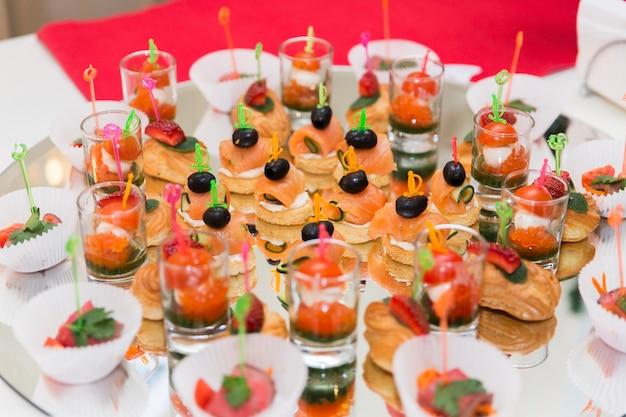 Dessert con pesce, pomodori e olive. tavola festiva con cibo gustoso