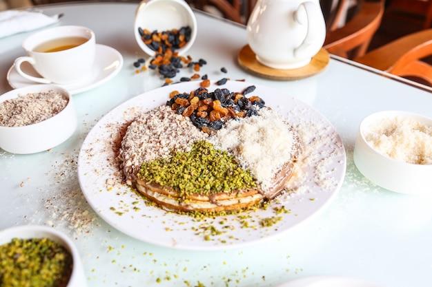 Dessert con pistacchio in polvere di zucchero e uva di vino essiccata in cima