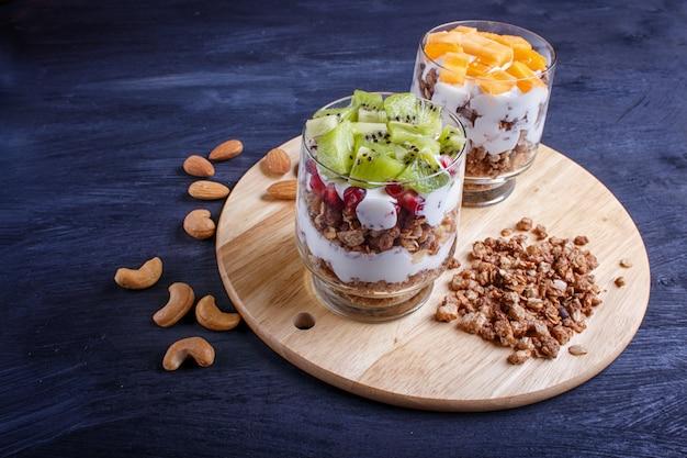Dessert con yogurt greco, muesli, mandorle, anacardi, kiwi e cachi sulla superficie in legno.