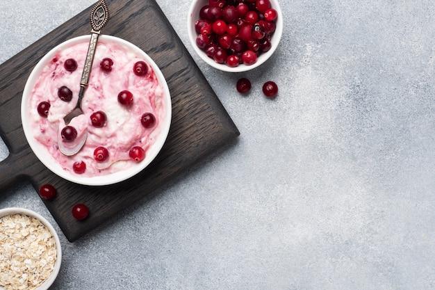 Dessert della ricotta dell'ostruzione e dei mirtilli rossi del yogurt su un piatto. tavolo in cemento grigio
