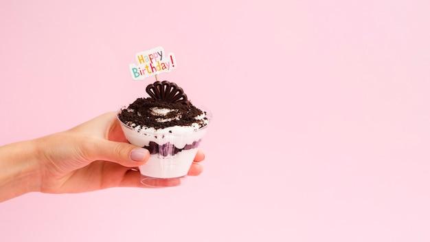 Dessert della tenuta della mano con il segno di buon compleanno