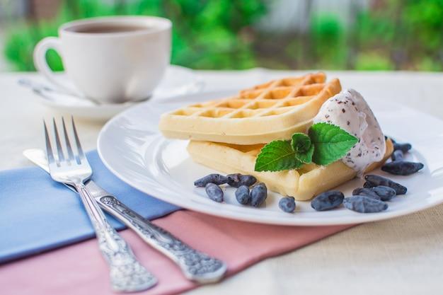 Dessert di cialde viennesi con gelato, frutti di bosco freschi e un rametto di menta.