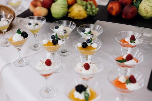Dessert di gelatina colorata con frutti di bosco e panna nella cristalleria sul buffet del banchetto