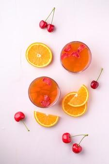 Dessert di gelatina con fragole in bicchiere con bacche di ciliegia e fettine di arancia, vista dall'alto, piatto disteso