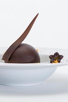 Dessert di lusso con globo di cioccolato e salsa alla vaniglia, servito su un biscotto, con cioccolato